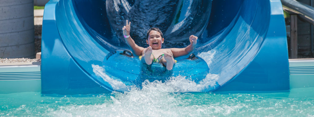 boy comes out of cyclone slide with a smile and peace sign